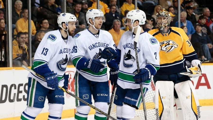 Vancouver Canucks right wing Jannik Hansen (36), of Denmark, is congratulated by Nick Bonino (13) and Dan Hamhuis (2) after Hansen scored a goal against Nashville Predators goalie Pekka Rinne, right, of Finland, in the second period of an NHL hockey game Tuesday, March 31, 2015, in Nashville, Tenn. (AP Photo/Mark Humphrey)