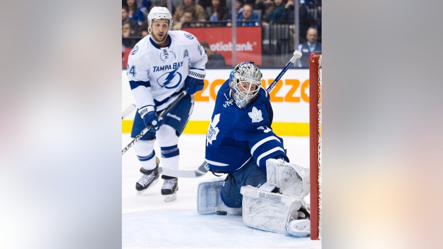 Toronto Maple Leafs goalie James Reimer, right, stops a shot as Tampa Bay Lightning forward Ryan Callahan (24) looks on during first period NHL hockey action in Toronto on Tuesday, March 31, 2015. (AP Photo/The Canadian Press, Nathan Denette)