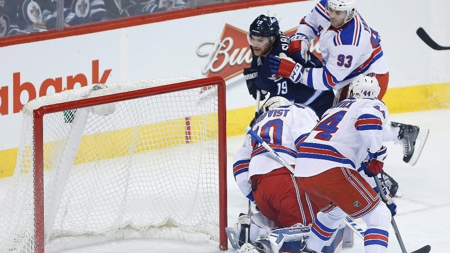Winnipeg Jets' Jim Slater (19) scores on New York Rangers goaltender Henrik Lundqvist (30) as Matt Hunwick (44) and Keith Yandle (93) defend during the first period of an NHL hockey game Tuesday, March 31, 2015, in Winnipeg, Manitoba. (AP Photo/The Canadian Press, John Woods)