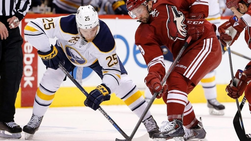 Buffalo Sabres' Mikhail Grigorenko (25), of Russia, battles Arizona Coyotes' Sam Gagner (9) for the puck after a face-off during the first period of an NHL hockey game Monday, March 30, 2015, in Glendale, Ariz. (AP Photo/Ross D. Franklin)