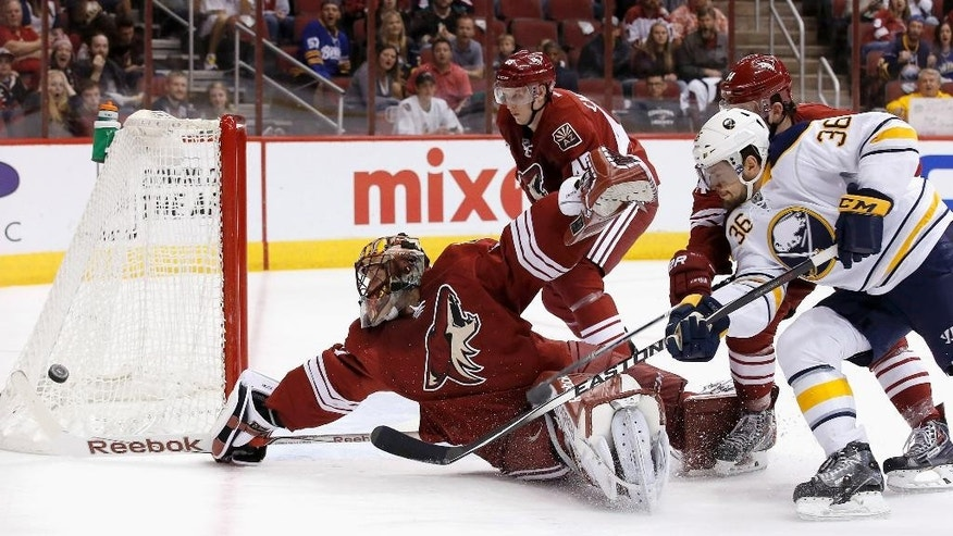 Buffalo Sabres' Patrick Kaleta (36) gets his shot turned away by a diving Arizona Coyotes' Mike Smith, left, as Coyotes' Andrew Campbell (45) and Joe Vitale (14) arrive late to defend during the first period of an NHL hockey game Monday, March 30, 2015, in Glendale, Ariz. (AP Photo/Ross D. Franklin)
