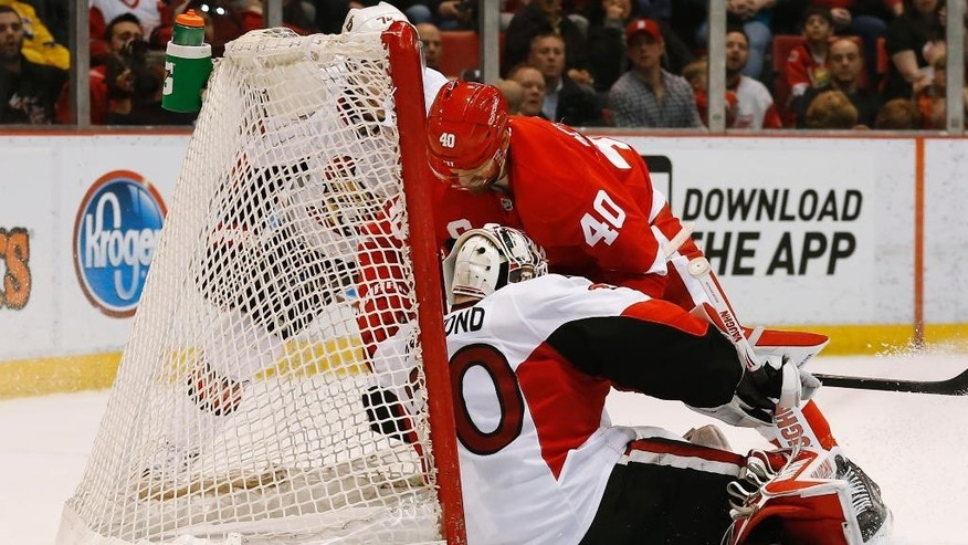 Detroit Red Wings left wing Henrik Zetterberg (40) lands on Ottawa Senators goalie Andrew Hammond (30) in the second period of an NHL hockey game in Detroit Tuesday, March 31, 2015. (AP Photo/Paul Sancya)