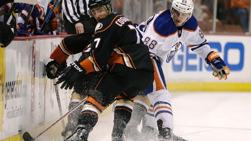 Anaheim Ducks' Andrew Cogliano, left, and Edmonton Oilers' Brandon Davidson fight for the puck during the first period of an NHL hockey game Wednesday, April 1, 2015, in Anaheim, Calif. (AP Photo/Jae C. Hong)