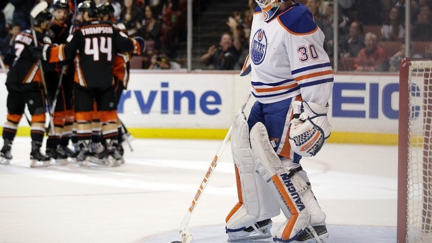 Edmonton Oilers goalie Ben Scrivens stands in front of the net as Anaheim Ducks players celebrate a goal by Simon Despres during the second period of an NHL hockey game Wednesday, April 1, 2015, in Anaheim, Calif. (AP Photo/Jae C. Hong)