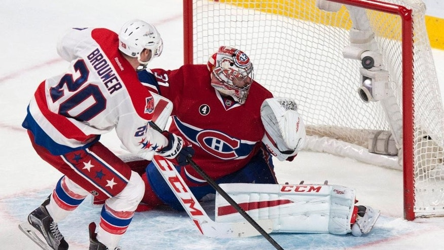 Washington Capitals' Troy Brouwer scores past Montreal Canadiens goalie Carey Price in the shootout of an NHL hockey game Thursday, April 2, 2015, in Montreal. Washington won 5-4. (AP Photo/The Canadian Press, Paul Chiasson)