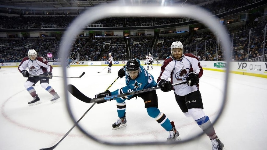 San Jose Sharks' Matt Nieto, center, vies for the puck against Colorado Avalanche's Zach Redmond, right, during the first period of an NHL hockey game Wednesday, April 1, 2015, in San Jose, Calif. (AP Photo/Marcio Jose Sanchez)