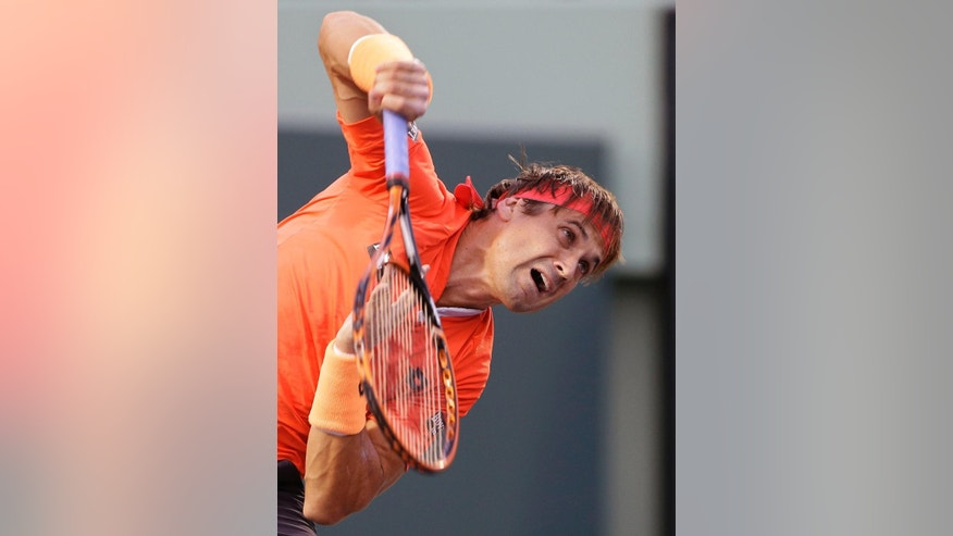 David Ferrer, of Spain, serves to Novak Djokovic, of Serbia, at the Miami Open tennis tournament, Thursday, April 2, 2015 in Key Biscayne, Fla. (AP Photo/Wilfredo Lee)