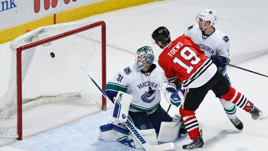 Chicago Blackhawks center Jonathan Toews (19) scores against Vancouver Canucks goalie Eddie Lack (31) during the third period of an NHL hockey game Thursday, April 2, 2015, in Chicago. The Blackhawks won 3-1. (AP Photo/Kamil Krzaczynski)