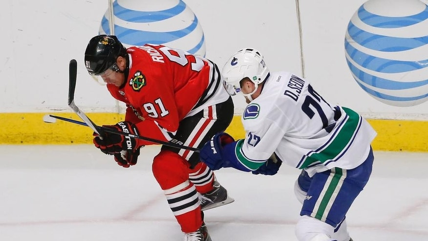 Chicago Blackhawks center Brad Richards (91) and Vancouver Canucks center Shawn Matthias (27) compete for the puck during the second period of an NHL hockey game Thursday, April 2, 2015, in Chicago. (AP Photo/Kamil Krzaczynski)