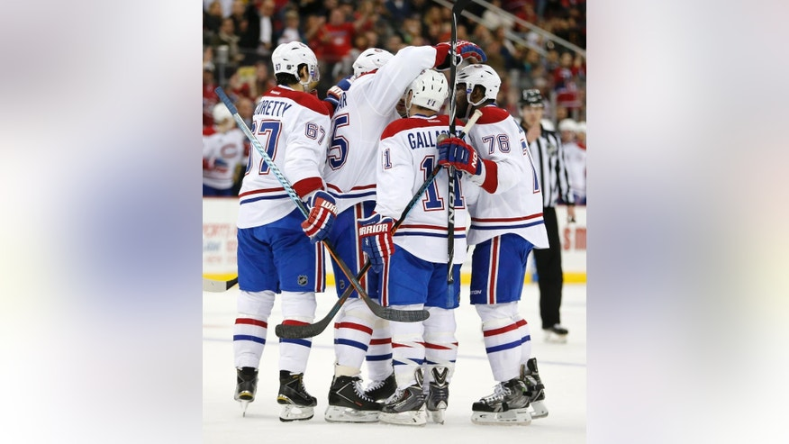 Montreal Canadiens players celebrate after Tomas Plekanec (14), of the Czech Republic, scored a goal against the New Jersey Devils during the first period of an NHL hockey game, Friday, April 3, 2015, in Newark, N.J. (AP Photo/Julio Cortez)