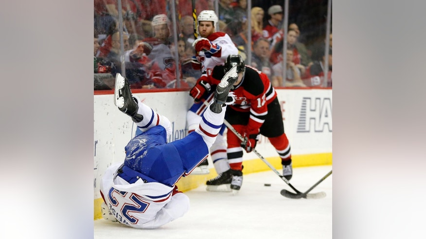 Montreal Canadiens right wing Dale Weise, left, rolls on his shoulder after hitting the boards as New Jersey Devils center Reid Boucher (12) battles for the puck with Brandon Prust, back, during the first period of an NHL hockey game, Friday, April 3, 2015, in Newark, N.J. (AP Photo/Julio Cortez)