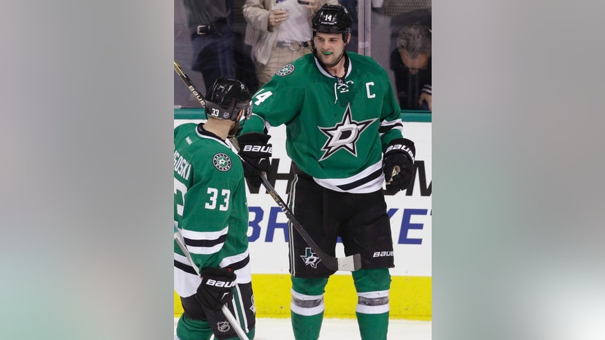Dallas Stars left wing Jamie Benn (14) celebrates his goal with defenseman Alex Goligoski (33) during the second period of an NHL hockey game against the St. Louis Blues on Friday, April 3, 2015, in Dallas. (AP Photo/LM Otero)