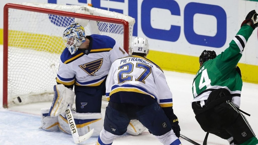 Dallas Stars left wing Jamie Benn (14) scores against St. Louis Blues goalie Brian Elliott (1) and defenseman Alex Pietrangelo (27) during the second period of an NHL hockey game Friday, April 3, 2015, in Dallas. (AP Photo/LM Otero)