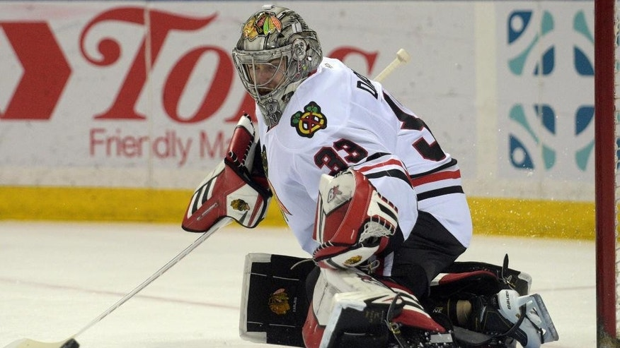 Chicago Blackhawks goaltender Scott Darling deflects the puck during the first period of an NHL hockey game against the Buffalo Sabres, Friday, April 3, 2015, in Buffalo, N.Y. (AP Photo/Gary Wiepert)