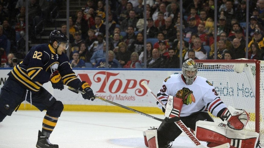 Buffalo Sabres left wing Marcus Foligno (82) shoots against Chicago Blackhawks goaltender Scott Darling during the first period of an NHL hockey game Friday, April 3, 2015, in Buffalo, N.Y. (AP Photo/Gary Wiepert)