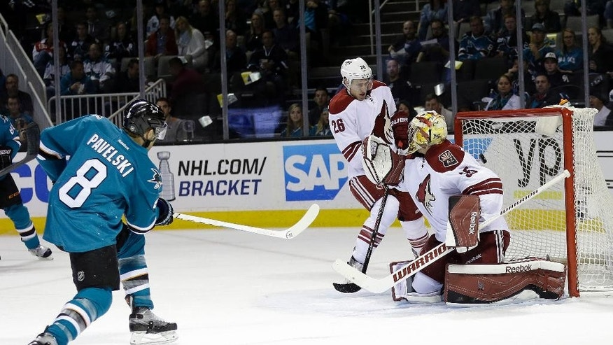 San Jose Sharks' Joe Pavelski (8) scores past Arizona Coyotes goalie Louis Domingue during the first period of an NHL hockey game Friday, April 3, 2015, in San Jose, Calif. (AP Photo/Marcio Jose Sanchez)