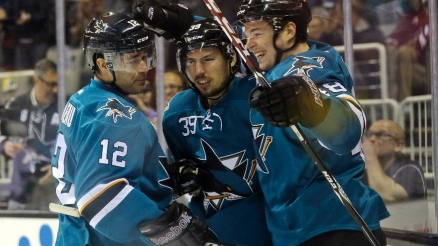San Jose Sharks' Logan Couture, center, celebrates his goal with teammates Patrick Marleau (12) and Tomas Hertl during the first period of an NHL hockey game against the Arizona Coyotes, Friday, April 3, 2015, in San Jose, Calif. (AP Photo/Marcio Jose Sanchez)