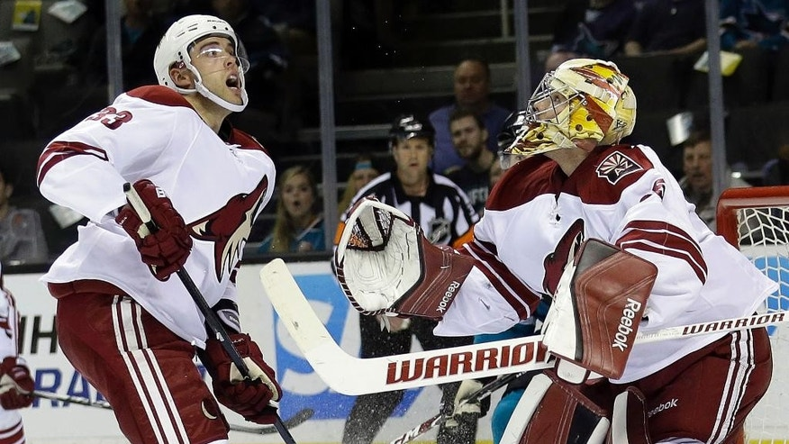 Arizona Coyotes goalie Louis Domingue, right, eyes the puck alongside teammate Brandon Gormley (33) during the first period of an NHL hockey game against the San Jose Sharks, Friday, April 3, 2015, in San Jose, Calif. (AP Photo/Marcio Jose Sanchez)