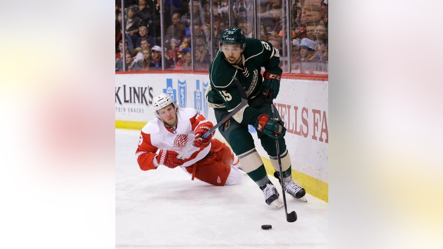 Minnesota Wild defenseman Matt Dumba (55) controls the puck in front of Detroit Red Wings left wing Justin Abdelkader (8) during the second period of an NHL hockey game in St. Paul, Minn., Saturday, April 4, 2015. The Red Wings won 3-2 in a shootout. (AP Photo/Ann Heisenfelt)
