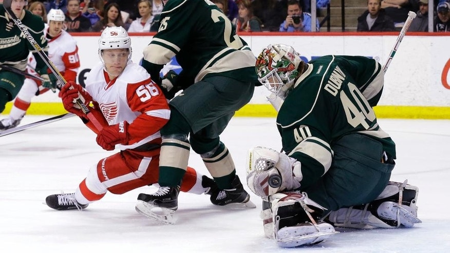 Minnesota Wild goalie Devan Dubnyk (40) deflects a shot in front of Detroit Red Wings left wing Teemu Pulkkinen (56), of Finland, and  Wild defenseman Jonas Brodin, center, during the second period of an NHL hockey game in St. Paul, Minn., Saturday, April 4, 2015. (AP Photo/Ann Heisenfelt)