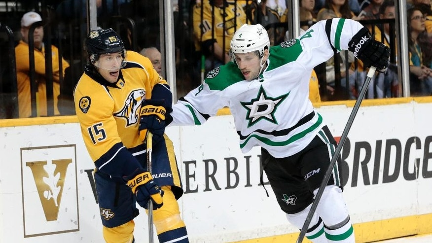 Nashville Predators center Craig Smith (15) passes the puck as he is defended by Dallas Stars' Jason Demers (4) in the first period of an NHL hockey game, Saturday, April 4, 2015, in Nashville, Tenn. (AP Photo/Mark Humphrey)
