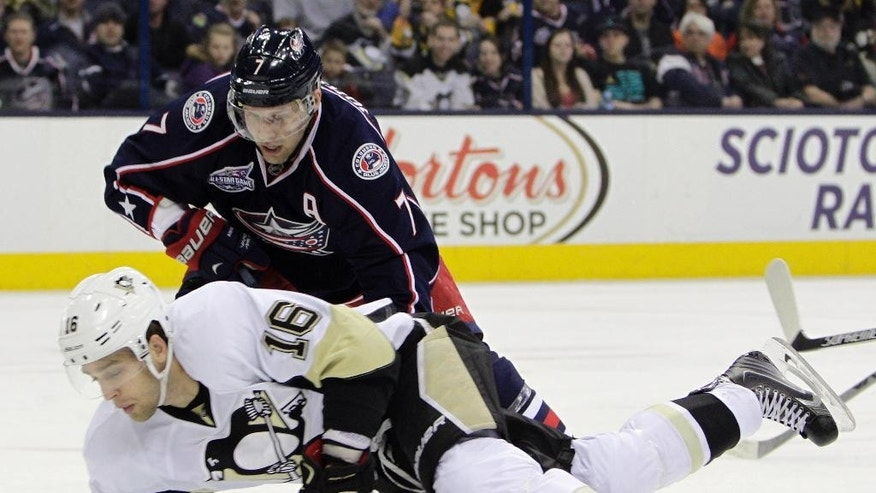 Columbus Blue Jackets' Jack Johnson, top, knocks Pittsburgh Penguins' Brandon Sutter to the ice during the first period of an NHL hockey game Saturday, April 4, 2015, in Columbus, Ohio. (AP Photo/Jay LaPrete)