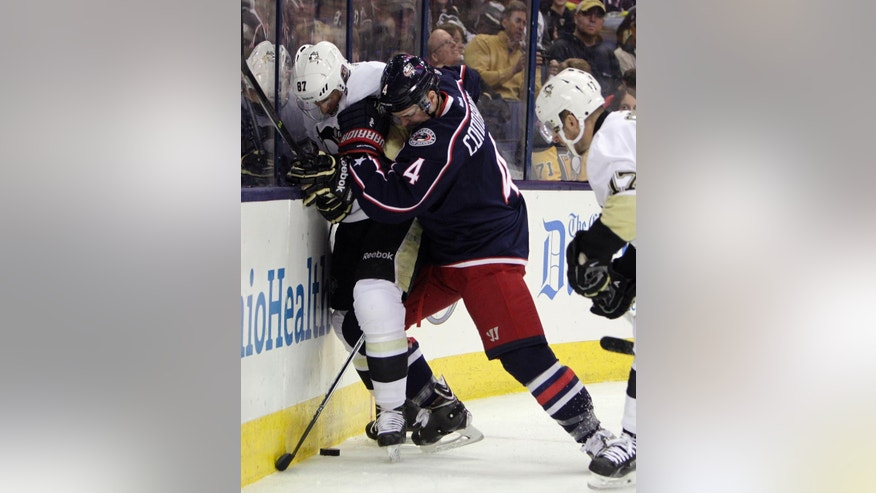 Columbus Blue Jackets' Kevin Connauton, right, and Pittsburgh Penguins' Sidney Crosby battle for the puck during the first period of an NHL hockey game Saturday, April 4, 2015, in Columbus, Ohio. (AP Photo/Jay LaPrete)
