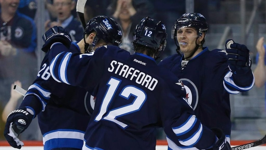 Winnipeg Jets' Blake Wheeler (26), Drew Stafford (12) and Mark Scheifele (55) celebrate Scheifele's goal against the Vancouver Canucks during the second period of an NHL game in Winnipeg, Manitoba, Saturday, April 4, 2015. (AP Photo/The Canadian Press, John Woods)