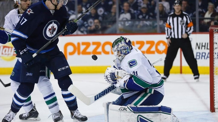 Vancouver Canucks' goaltender Eddie Lack (31) keeps his eye on the rebound as Winnipeg Jets' Adam Lowry (17) and Canucks' Christopher Tanev (8) look on during second period NHL action in Winnipeg, Manitoba, on Saturday, April 4, 2015. (AP Photo/The Canadian Press, John Woods)