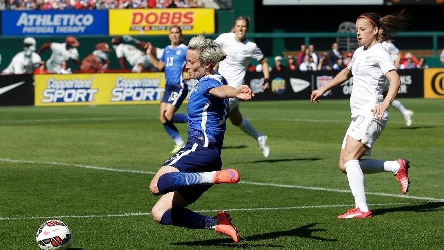United States' Megan Rapinoe, left, tries to get off a shot as New Zealand's Ria Percival, right, gives chase during the first half of an exhibition soccer match, Saturday, April 4, 2015, in St. Louis. (AP Photo/Jeff Roberson)