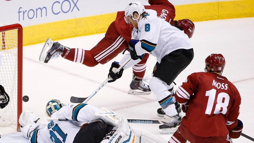 San Jose Sharks' Antti Niemi (31), of Finland, makes a diving save on a shot by Arizona Coyotes' Sam Gagner, top, as Sharks' Joe Pavelski (8) defends and Coyotes' David Moss (18) looks on during the second period of an NHL hockey game Saturday, April 4, 2015, in Glendale, Ariz. (AP Photo/Ross D. Franklin)
