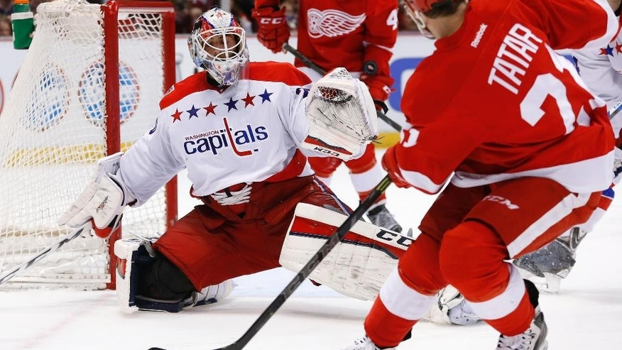 Washington Capitals goalie Braden Holtby (70) defends a Detroit Red Wings left wing Tomas Tatar (21) shoots in the second period of an NHL hockey game in Detroit Sunday, April 5, 2015. (AP Photo/Paul Sancya)