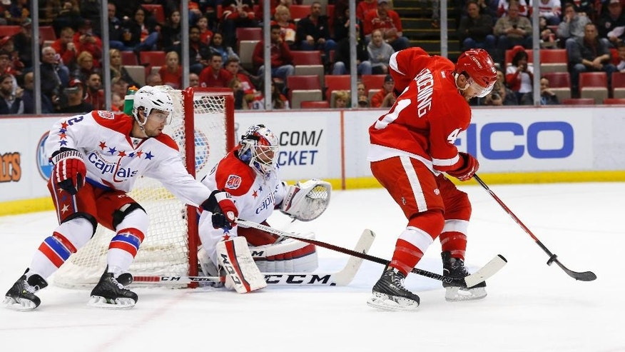 Detroit Red Wings right wing Luke Glendening (41) tries to redirect a shot at Washington Capitals goalie Braden Holtby (70) as Matt Niskanen (2) defends in the second period of an NHL hockey game in Detroit Sunday, April 5, 2015. (AP Photo/Paul Sancya)