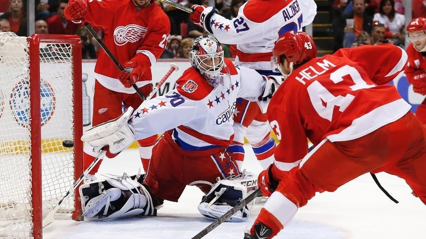 Detroit Red Wings center Darren Helm (43) scores on Washington Capitals goalie Braden Holtby (70) in the second period of an NHL hockey game in Detroit Sunday, April 5, 2015. (AP Photo/Paul Sancya)