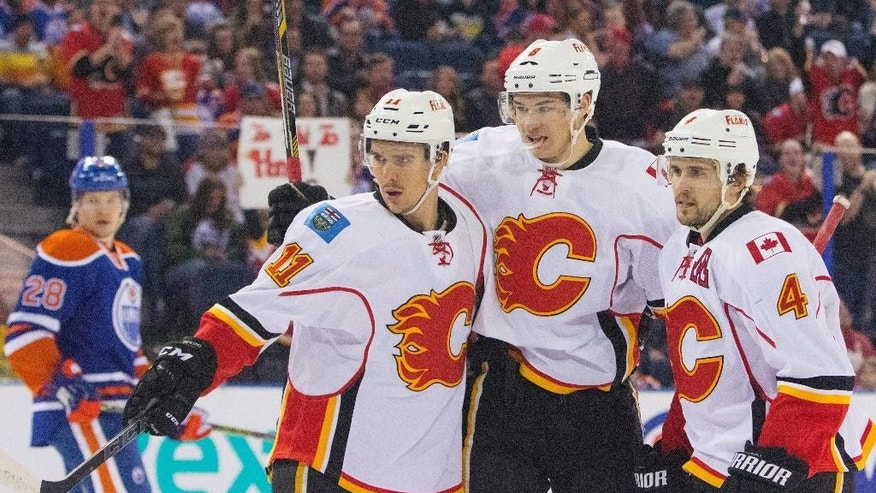Calgary Flames' Joe Colborne (8) celebrates his goal with Mikael Backlund (11) and Kris Russell as Edmonton Oilers' Matt Fraser (28) skates off during the first period of an NHL hockey game Saturday, April 4, 2015, in Edmonton, Alberta. (AP Photo/The Canadian Press, Amber Bracken)