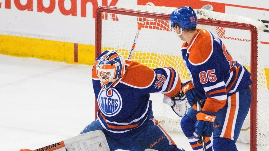 Edmonton Oilers goalie Ben Scrivens (30) and Martin Marincin (85) look for the puck as it slides through the crease during the second period of the Oilers' NHL hockey game against the Calgary Flames on Saturday, April 4, 2015, in Edmonton, Alberta. (AP Photo/The Canadian Press, Amber Bracken)
