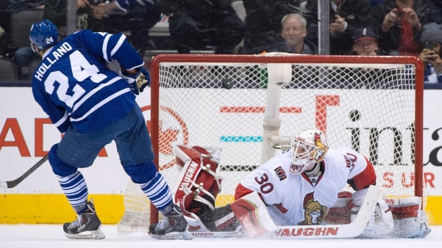 Toronto Maple Leafs centre Peter Holland scores the game-winning overtime shootout goal against Ottawa Senators goaltender Andrew Hammond in an NHL hockey game in Toronto, Sunday, April 5, 2015. (AP Photo/The Canadian Press, Frank Gunn)