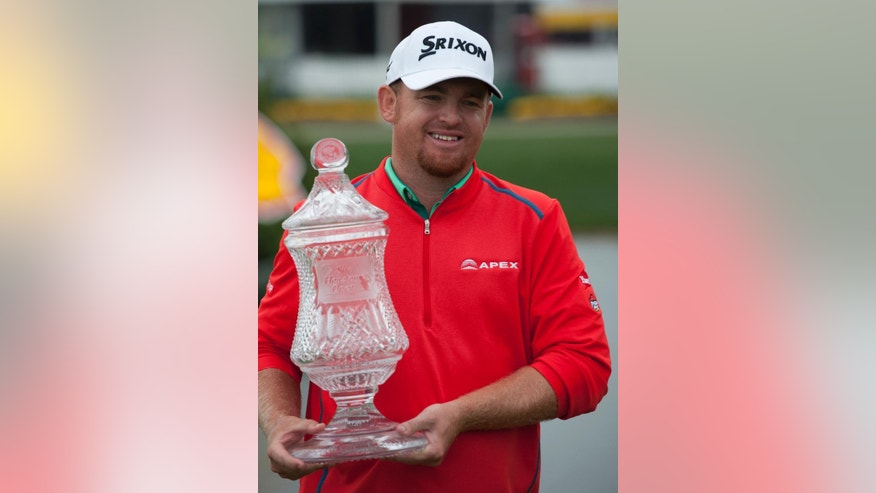 J.B. Holmes posses with the trophy after winning the Houston Open golf tournament in a playoff Sunday, April 5, 2015, in Humble, Texas. (AP Photo/George Bridges)