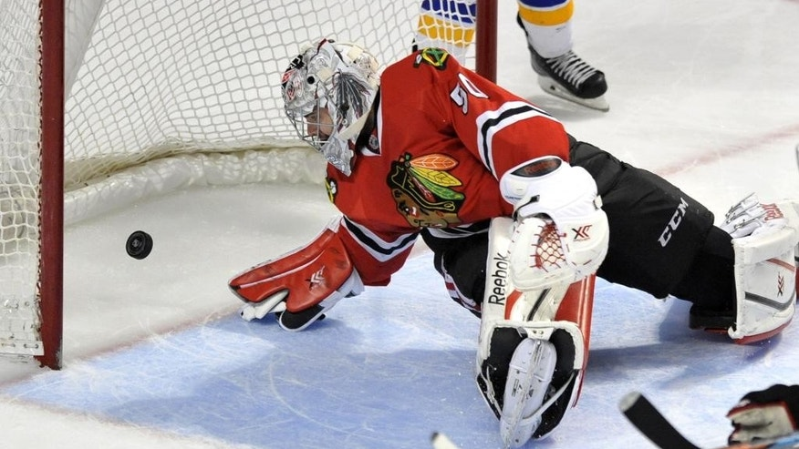 Chicago Blackhawks goalie Corey Crawford (50), misses a goal by St. Louis Blues' Olli Jokinen (13) of Finland, during the second period of an NHL hockey game Sunday, April 5, 2015, in Chicago. (AP Photo/Paul Beaty)