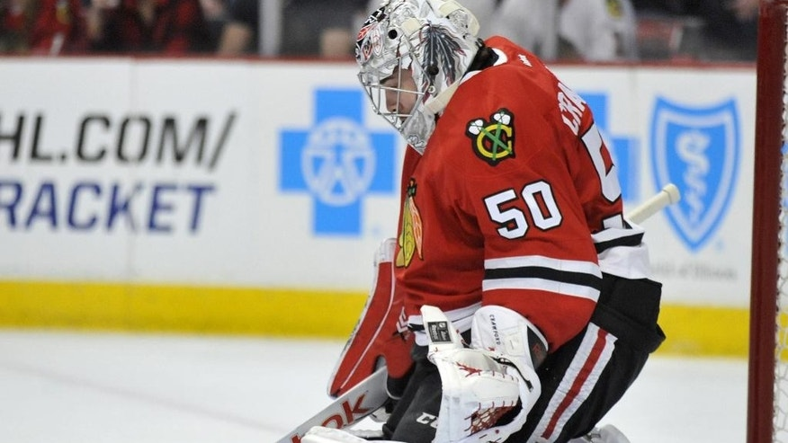 Chicago Blackhawks goalie Corey Crawford (50), makes a save during the first period of an NHL hockey game against the St. Louis Blues Sunday, April 5, 2015, in Chicago. (AP Photo/Paul Beaty)