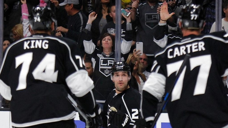 Los Angeles Kings defenseman Alec Martinez, center, reacts at left wing Dwight King (74) and center Jeff Carter (77) after scoring against the Colorado Avalanche during the second period of an NHL hockey game in Los Angeles, Saturday, April 4, 2015. (AP Photo/Alex Gallardo)