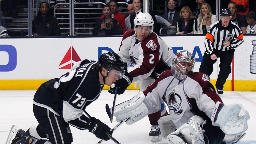 Los Angeles Kings center Tyler Toffoli,left, has his shot blocked by Colorado Avalanche goalie Semyon Varlamov, right, of Russia, with defenseman Nick Holden (2) looking on during the second period of an NHL hockey game in Los Angeles, Saturday, April 4, 2015. (AP Photo/Alex Gallardo)