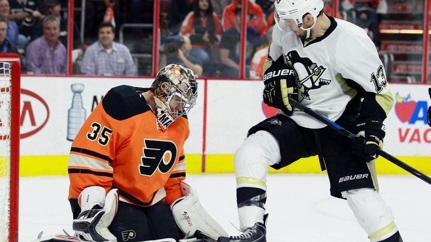 Philadelphia Flyers goalie Steve Mason, left, and Pittsburgh Penguins' Nick Spaling watch the puck in the third period of an NHL hockey game Sunday, April 5, 2015, in Philadelphia. The Flyers won 4-1. (AP Photo/Tom Mihalek)