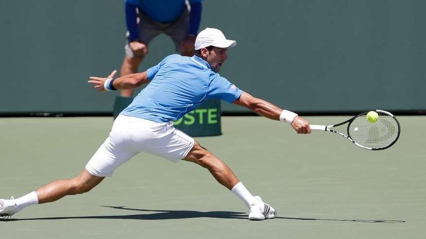 Novak Djokovic, of Serbia,  returns to Andy Murray, of Great Britain, during the men's final match at the Miami Open tennis tournament Sunday, April 5, 2015, in Key Biscayne, Fla. (AP Photo/Alan Diaz)