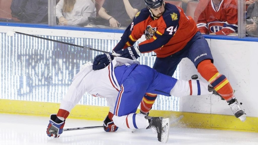 Florida Panthers defenseman Erik Gudbranson, right, and Montreal Canadiens center Torrey Mitchell battle for the puck during the first period of an NHL hockey game Sunday, April 5, 2015 in Sunrise, Fla. (AP Photo/Wilfredo Lee)