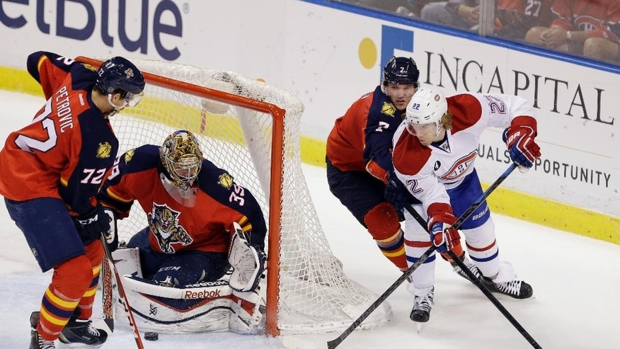 Montreal Canadiens right wing Dale Weise (22) attempts a shot against Florida Panthers goalie Dan Ellis (39) defenseman Alex Petrovic (72) and defenseman Dmitry Kulikov, of Russia, during the first period of an NHL hockey game Sunday, April 5, 2015 in Sunrise, Fla. (AP Photo/Wilfredo Lee)