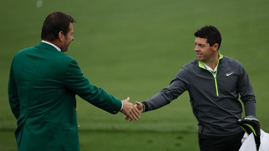 Rory McIlroy, of Northern Ireland, shakes hands with former golfing champion Nick Faldo, left, during a practice round for the Masters golf tournament Monday, April 6, 2015, in Augusta, Ga. (AP Photo/Chris Carlson)