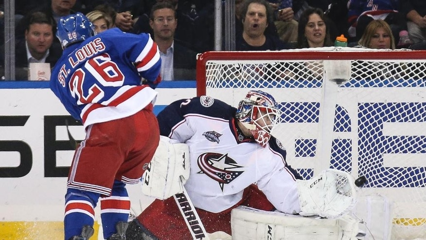 New York Rangers right wing Martin St. Louis (26) scores on Columbus Blue Jackets goalie Sergei Bobrovsky (72) during the first period of an NHL hockey game, Monday, April 6, 2015, in New York. (AP Photo/John Minchillo)