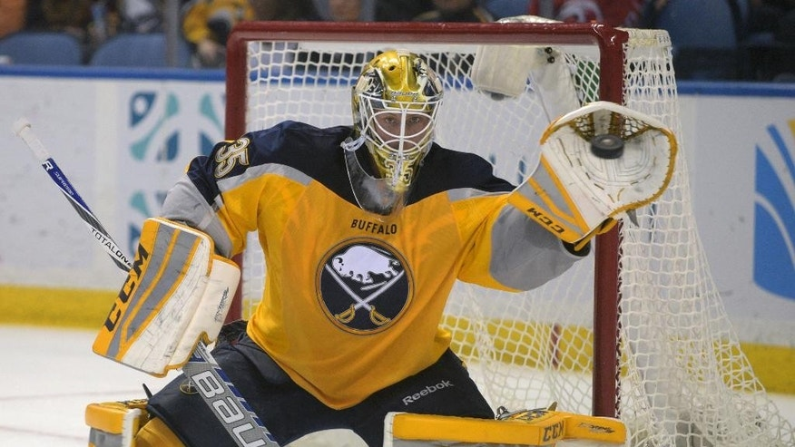 Buffalo Sabres goaltender Anders Lindback (35), of Sweden, makes a glove save during the second period of an NHL hockey game against the Carolina Hurricanes Monday, April 6, 2015, in Buffalo, N.Y. (AP Photo/Gary Wiepert)