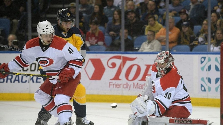 Buffalo Sabres center Cody Hodgson (19) battles alongside the net with Carolina Hurricanes defenseman Danny Biega (41) while goaltender Cam Ward (30) makes the save during the first period of an NHL hockey game Monday, April 6, 2015, in Buffalo, N.Y. (AP Photo/Gary Wiepert)